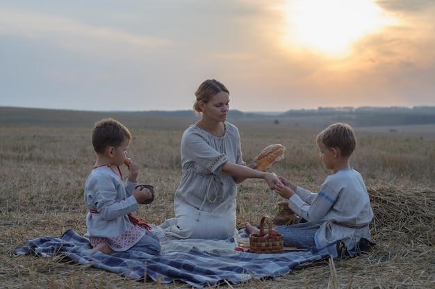 夏の夜の自然の中での家族のピクニック。母と息子は傾斜した麦畑でパン、牛乳、果物を食べる
