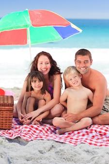 Семейный пикник под зонтиком на пляже