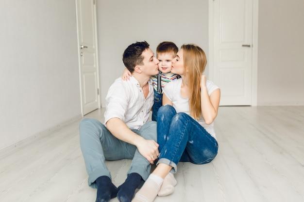 Семейное фото двух молодых родителей, играющих со своим мальчиком