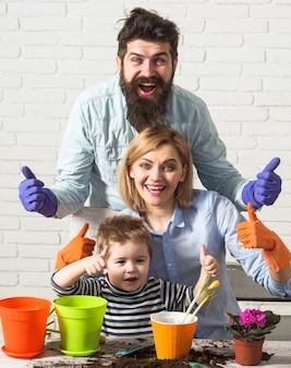 一緒に花を植える家族。息子は両親が植物の世話をするのを手伝います。