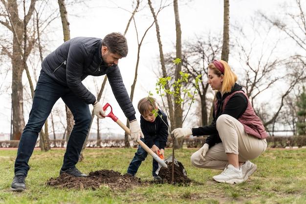 Famiglia che placca insieme un albero