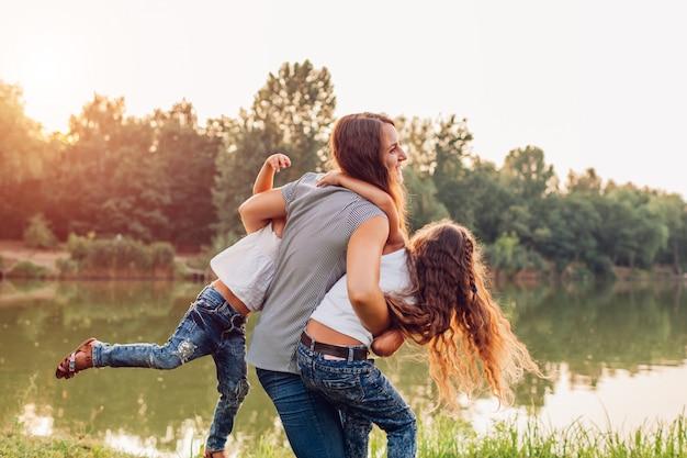 Семья играет и веселится у летней реки