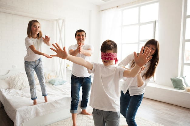 Family playing blind man's buff in bedroom