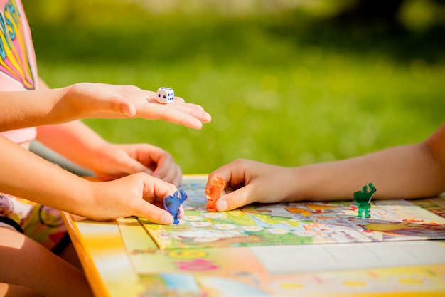 Family playing a board game, one kid is on the move and capturing the piece of another player.games in kindergarden. board game and kids leisure concept. kids holding red people figure in hand