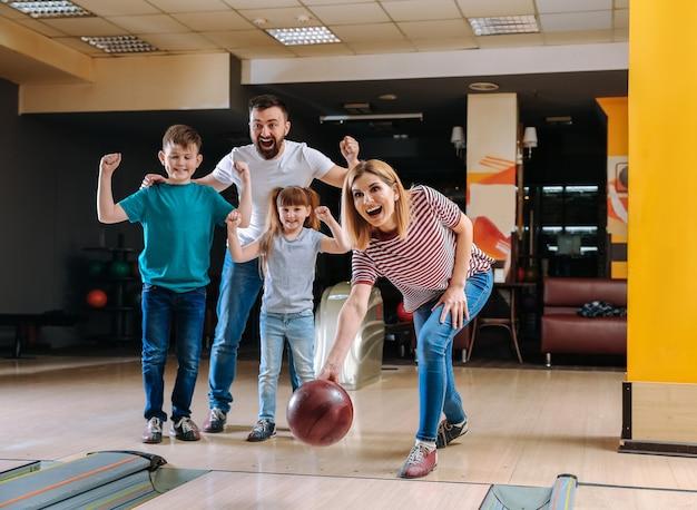 Семья играет в боулинг в клубе