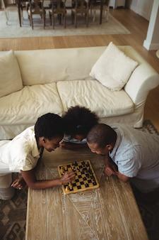 Семья играет в шахматы вместе дома в гостиной