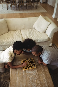 Family playing chess together at home in the living room