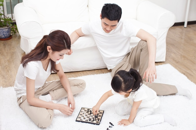 Family playing chess together at home