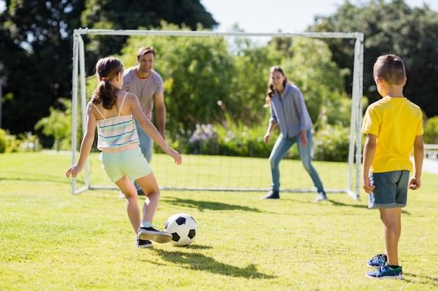Семья играет в футбол вместе в парке