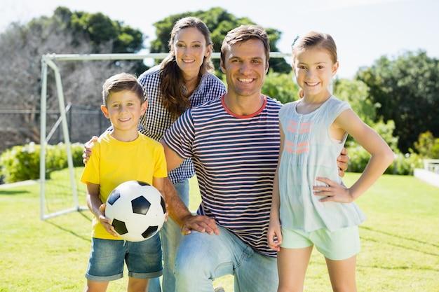 家族が公園でサッカーを一緒に遊んで