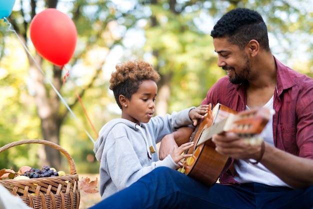 一緒にギターを弾く家族