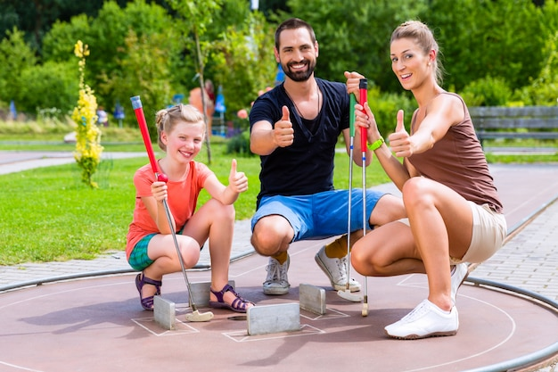 Family playing miniature golf on summer day