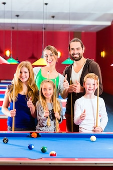 Family playing pool billiard game