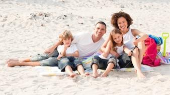 ビーチに座って遊んでいる家族