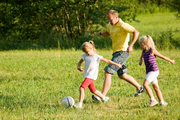 Family playing soccer in a grass field