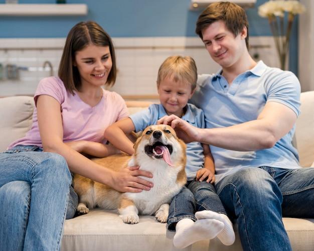 Семья играет вместе с милой собакой