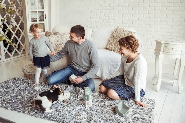 넓은 거실에서 애완견과 함께 노는 가족