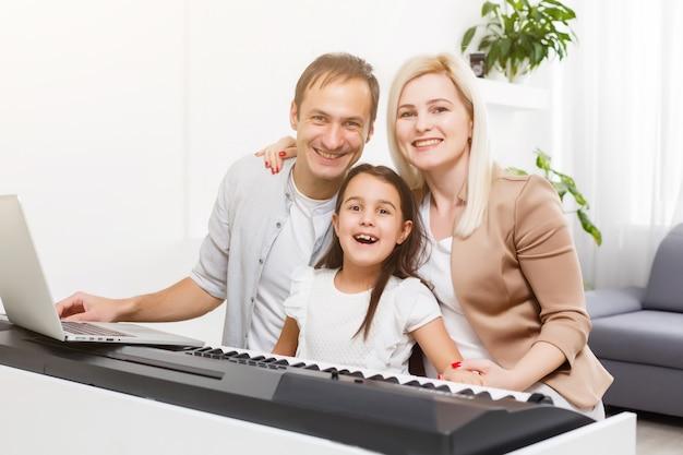 가족은 집에서 디지털 피아노를 연주하고, 온라인으로 학습하고, 격리 중 가족 휴식, 자가 격리, 온라인 교육 개념입니다. 사랑하는 사람 개념에 대한 지원