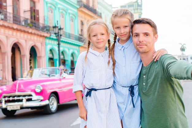 Family in popular area in old havana, cuba. portrait of two kids and young dad outdoors on a street of havana