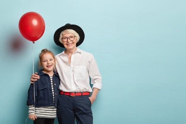Family portrait of granddaughter and granny embrace and celebrate holiday, hold air balloon, wear festive clothes, express positive emotions isolated on blue wall. generation and fest concept