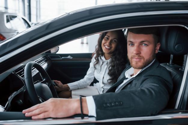 차량에있는 가족 초상화. 자동차 살롱에서 새 차를 시도하는 사랑스러운 성공적인 부부