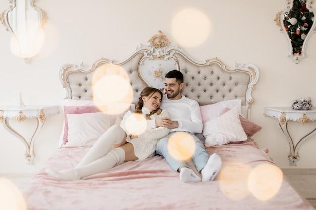 Семейный портрет. мужчина и женщина отдыхают на мягких серых порочках в комнате с елкой