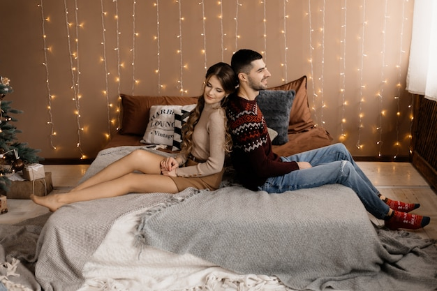 Family portrait. man and woman relax on soft grey bad in a room with christmas tree