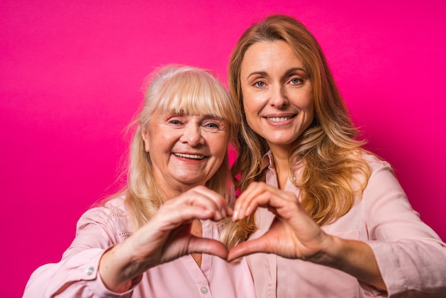 ピンクの壁に両手でハートを形成する家族の肖像画、中年の女性と年配の母親