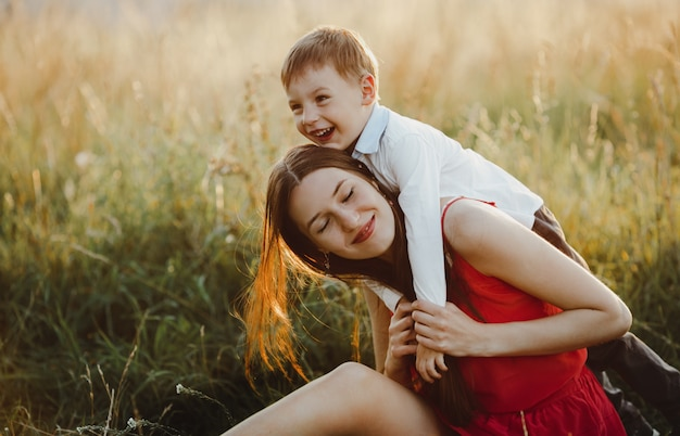 Family portrait, nature. charming mom and son play on the lawn b