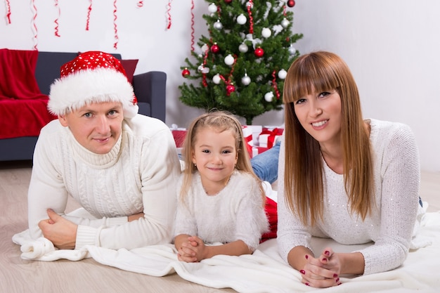 Family portrait near decorated christmas tree at home