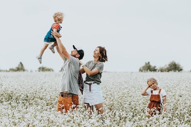 Семейный портрет молодой красивой пары с детьми на белом поле с цветами