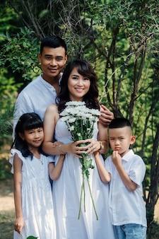 初秋の最後の暖かい日を楽しんで、公園で白い服を着て立っている幸せな愛情のあるアジアの両親とその子供たちの家族の肖像画。短い木の前。