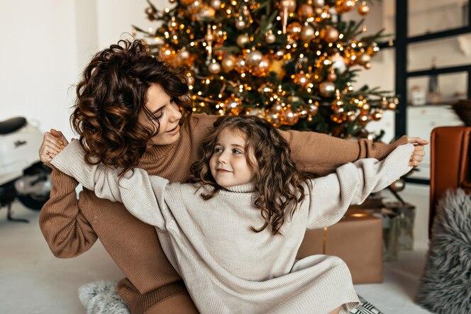幸せな若い母とかわいい素敵な娘の家族の肖像画を楽しんで、贈り物でクリスマスパーティーを祝う
