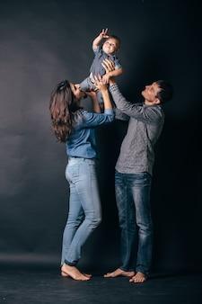 Семейный портрет родителей и ребенка в джинсовой одежде повседневного стиля. модные модели веселятся на сером фоне.