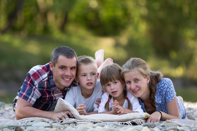 若い幸せな母、父、2人のかわいい金髪の子供、男の子と女の子の緑のボケ味を持つ明るい夏の日の家族の肖像画。幸せな家族関係、愛、ケア、完璧な休日のコンセプト