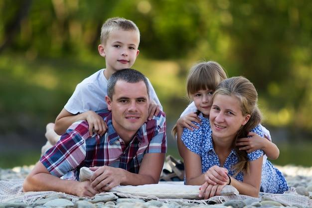 若い幸せな母、父および2人のかわいい金髪の子供、男の子と女の子の緑の明るい夏の日の家族の肖像画。幸せな家族関係、愛、ケア、完璧な休日のコンセプト