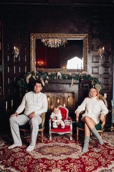 Family posing in decorated living room.adorable woman, man and baby wearing in cozy white knitted clothes.