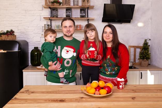 クリスマスの朝にキッチンでポーズをとる家族