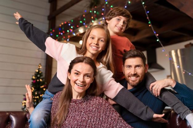 Семья вместе позирует возле елки