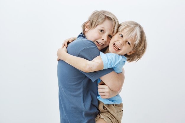 Family and positive emotions concept. satisfied happy blond boy hugging brother and gazing with pleased positive smile