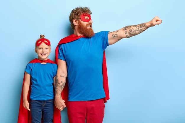 Family power concept. confident cheerful father and little daughter pretend being superheroes
