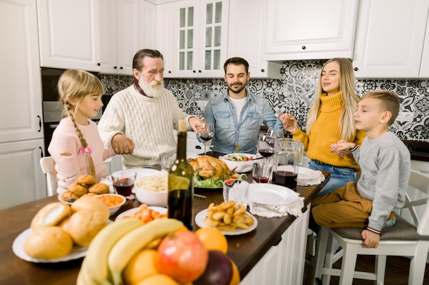 Family praying before holiday dinner on thanksgiving