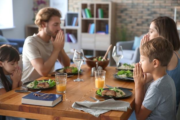 家で食事の前に祈る家族