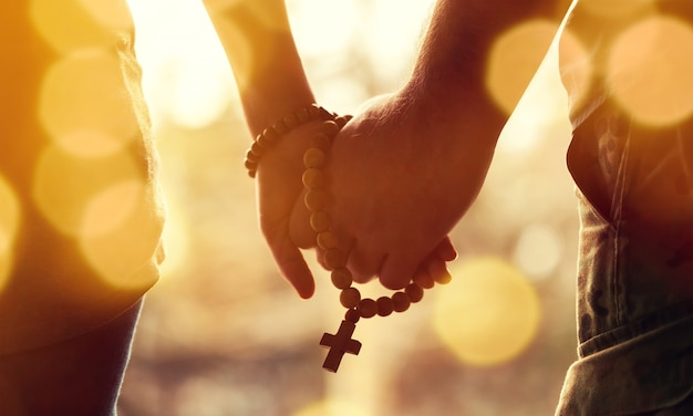 Family praying, closeup man and woman holding hands and prayer rope