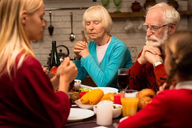 Family praying at the dinner table with eyes closed