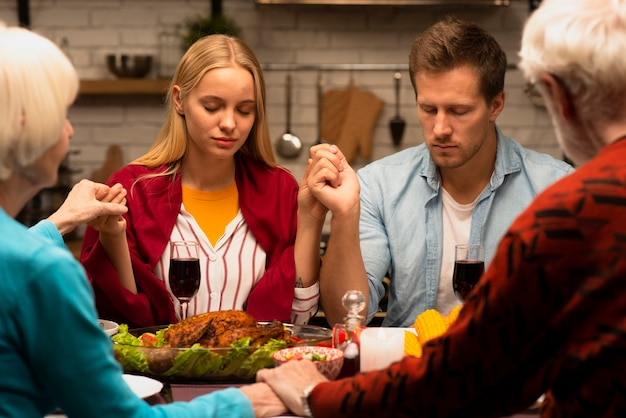 Family praying at the dinner table