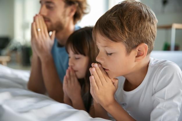 自宅のベッドの近くで祈る家族