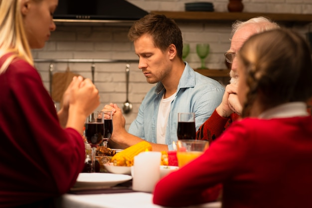 Family praying at the thanksgiving dinner table