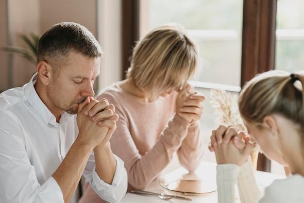 실내에서 식사하기 전에 함께기도하는 가족