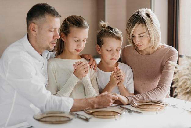 Famiglia che prega insieme prima di mangiare